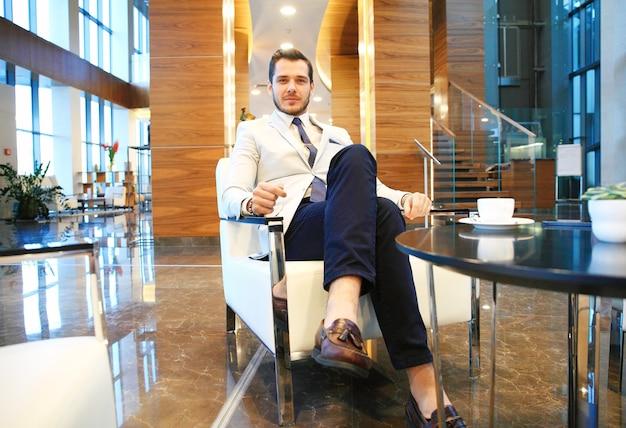 Retrato de um jovem empresário feliz sentado no sofá no saguão do hotel