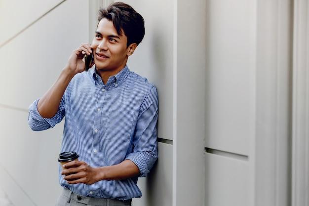 Retrato de um jovem empresário feliz usando telefone celular. estilo de vida das pessoas modernas. de pé junto à parede com uma xícara de café