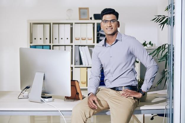 Retrato de um jovem empresário indiano positivo sentado em sua mesa de escritório e sorrindo para a câmera
