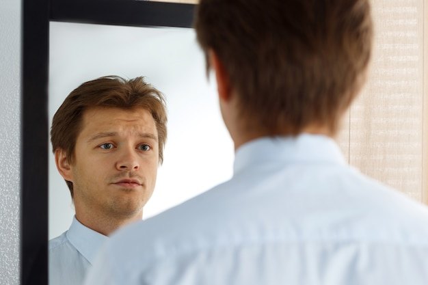 Retrato de um jovem empresário inseguro com cara infeliz, olhando no espelho. homem se preparando para uma reunião importante, nova entrevista de emprego ou namoro. relacionamento difícil, conceito de gerenciamento de estresse
