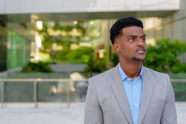 Retrato de um jovem empresário negro africano pensando ao ar livre