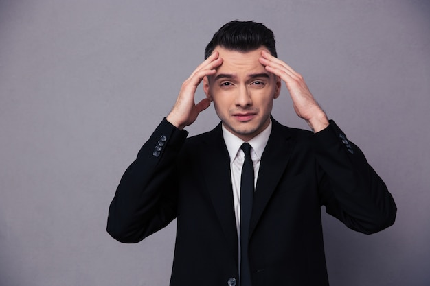 Retrato de um jovem empresário pensando sobre uma parede cinza