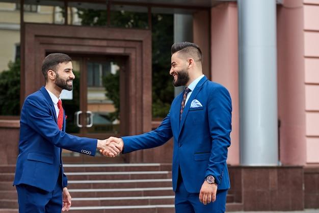 Retrato de um jovem empresário saudita cumprimentando seu parceiro de negócios com um aperto de mão na frente do centro de negócios ao ar livre