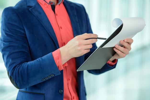 Retrato de um jovem empresário segurando documentos.