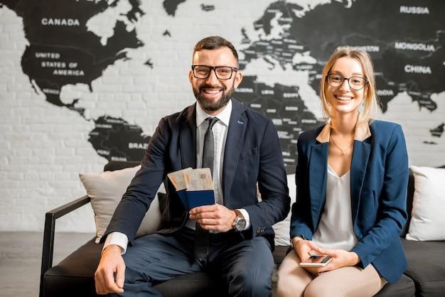 Retrato de um jovem empresário sentado no escritório da agência de viagens com um lindo mapa-múndi ao fundo