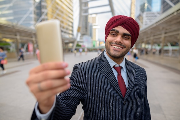 Retrato de um jovem empresário sikh indiano usando turbante enquanto explora a cidade de bangkok, tailândia