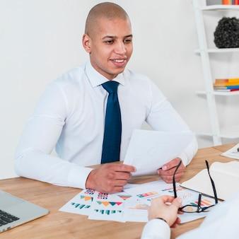 Retrato de um jovem empresário sorridente com relatórios de negócios na mesa, sentado com seu colega de trabalho