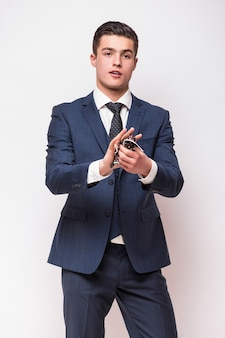 Retrato de um jovem empresário sorridente e feliz em um terno azul isolado na parede branca