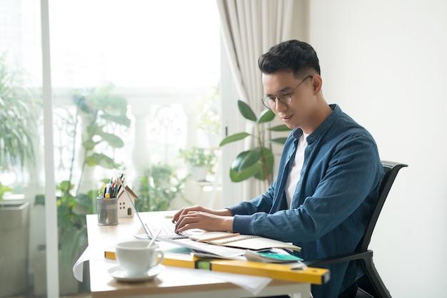 Retrato de um jovem empresário sorridente, trabalhando em projetos no escritório