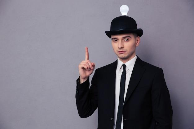 Retrato de um jovem empresário tendo uma ideia sobre uma parede cinza