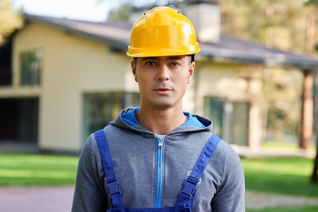 Retrato de um jovem engenheiro bonito com capacete olhando para a câmera posando ao ar livre enquanto