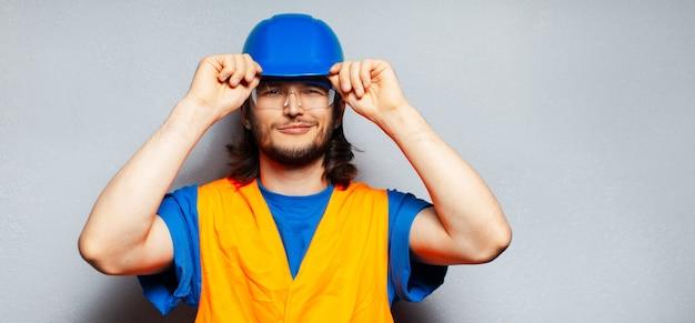 Retrato de um jovem engenheiro de construção confiante usando equipamento de segurança; capacete azul, óculos transparentes e colete amarelo.