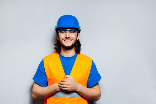 Retrato de um jovem engenheiro trabalhador da construção feliz usando equipamento de segurança; capacete azul, óculos transparentes e colete amarelo.