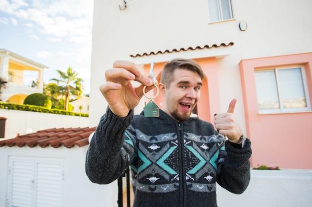 Retrato de um jovem engraçado segurando a chave da nova casa e gesticulando com o polegar para a nova casa ou apartamento