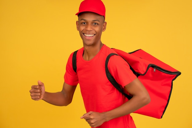 Retrato de um jovem entregador aparecendo o polegar.
