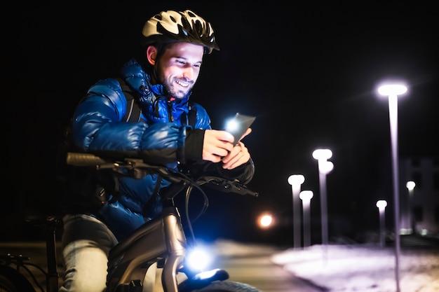 Retrato de um jovem entregador com bicicleta verifica os endereços de um cliente usando seu smartphone com gps à noite em um parque fora da cidade.
