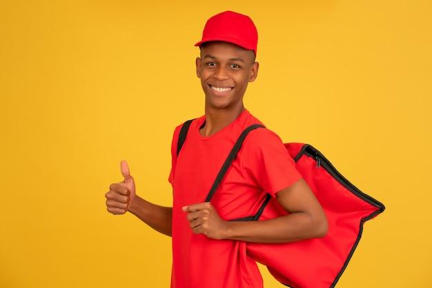 Retrato de um jovem entregador, olhando para a câmera e mostrando o polegar em pé contra um fundo amarelo isolado. conceito de serviço de entrega.