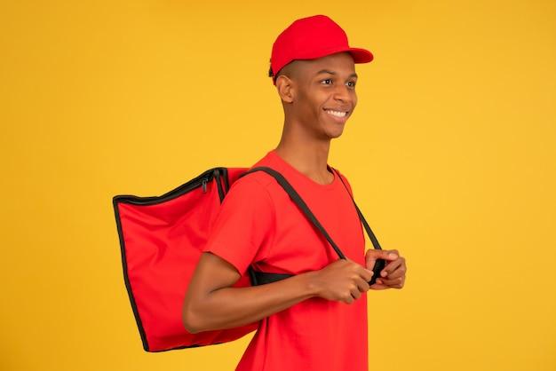 Retrato de um jovem entregador, olhando para a câmera em pé contra um fundo amarelo isolado. conceito de serviço de entrega.
