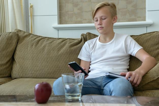 Retrato de um jovem escandinavo bonito com cabelos loiros na sala de estar em casa