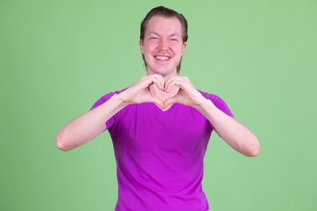 Retrato de um jovem escandinavo bonito vestindo uma camisa roxa contra o chroma key ou uma parede verde