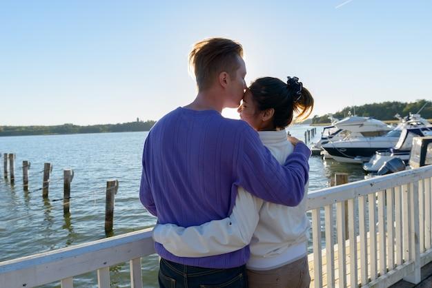 Retrato de um jovem escandinavo e uma jovem mulher asiática como um casal multiétnico, juntos e apaixonados no cais ao ar livre