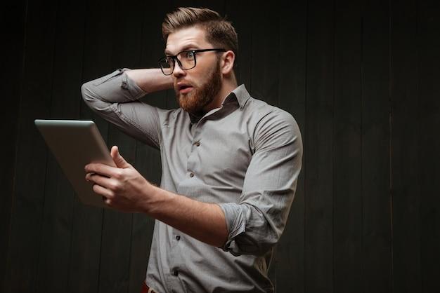 Retrato de um jovem espantado com óculos, segurando um computador tablet e gesticulando, isolado em uma superfície de madeira preta