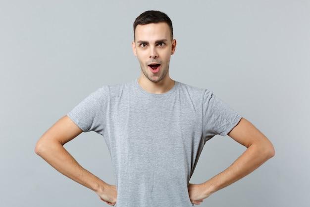 Retrato de um jovem espantado e perplexo com roupas casuais em pé com as mãos nos quadris na cintura