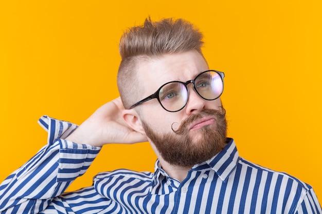 Retrato de um jovem estudante do sexo masculino positivo com um penteado elegante, óculos e barba, posando em uma parede amarela. conceito de barbearia e salão de beleza para homens.