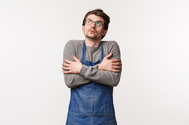 Retrato de um jovem estudante do sexo masculino que trabalha meio período na cafeteria, quebre o suporte ao ar livre no avental e olhe para cima enquanto sentir frio, tremendo e se abraçar do tempo frio,