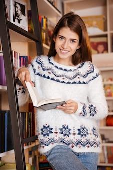 Retrato de um jovem estudante sorridente lendo um livro na estante da biblioteca