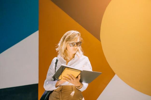 Retrato, de, um, jovem, executiva, livro leitura, ficar, contra, papel parede