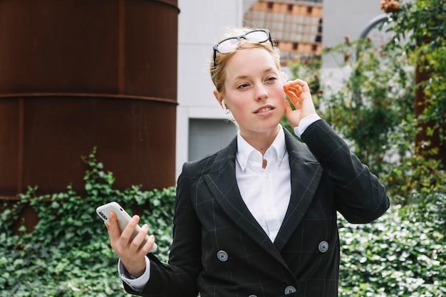 Retrato, de, um, jovem, executiva, segurando, telefone móvel, em, mão, escutar, ligado, bluetooth
