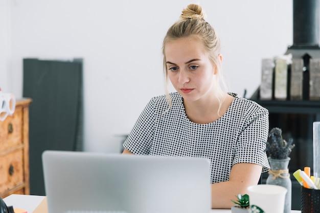 Retrato, de, um, jovem, executiva, trabalhar, laptop, em, escritório