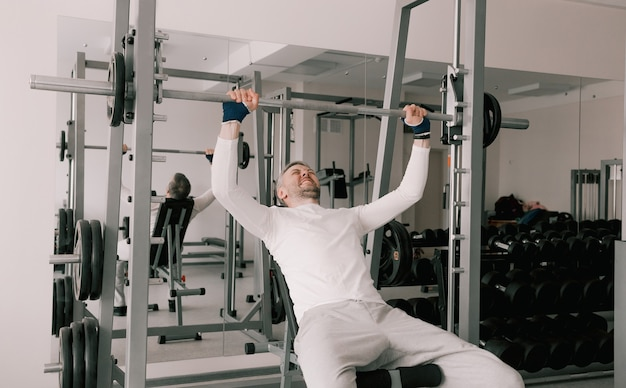 Retrato de um jovem fazendo exercícios físicos, com um rosto tenso, treinando com uma barra, sentado em um banco na academia. em uma camiseta branca. estilo de vida saudável