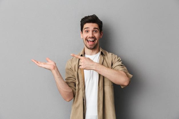 Retrato de um jovem feliz, apontando para o espaço da cópia