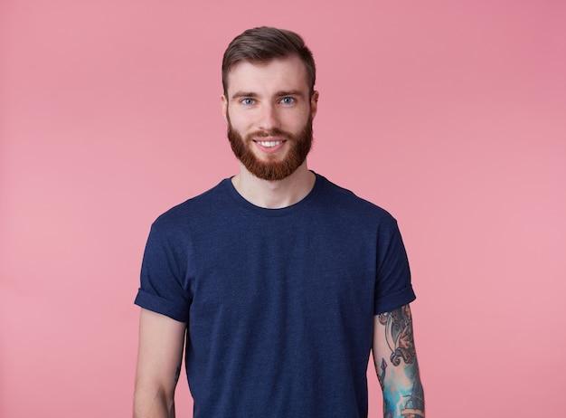 Retrato de um jovem feliz atraente barbudo vermelho com olhos azuis, vestindo uma camiseta azul, sorrindo e olhando para a câmera isolada sobre fundo rosa.
