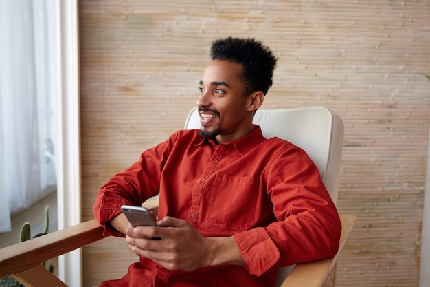Retrato de um jovem feliz barbudo encaracolado de cabelos curtos com pele escura, segurando o smartphone nas mãos e olhando alegremente pela janela, isolado no interior da casa