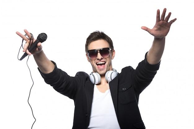 Retrato de um jovem feliz com um microfone.