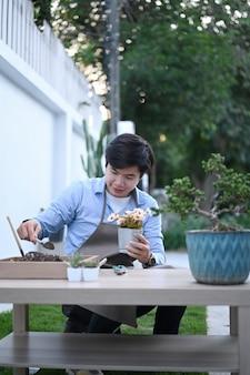 Retrato de um jovem feliz está plantando flores no vaso em seu jardim doméstico.