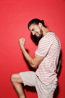 Retrato de um jovem feliz isolado no vermelho