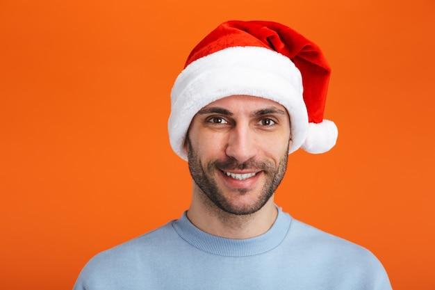 Retrato de um jovem feliz otimista positivo no chapéu de papai noel de natal posando isolado sobre uma parede laranja.