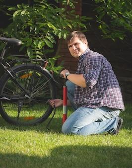 Retrato de um jovem feliz sentado na grama e no parque bombeando pneus