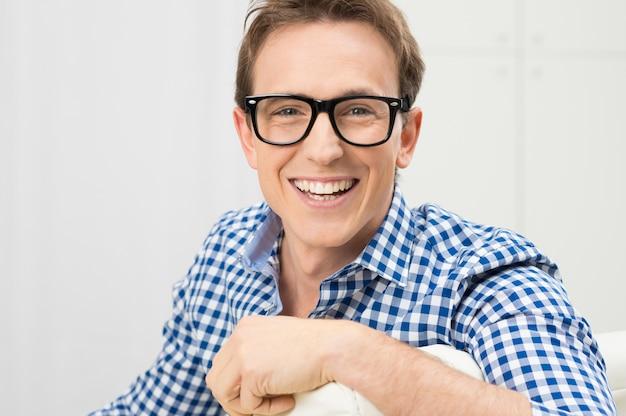Retrato de um jovem feliz usando óculos