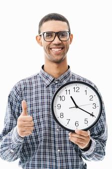 Retrato de um jovem feliz vestindo uma camisa xadrez em pé sobre o branco, mostrando o relógio de parede com o polegar para cima