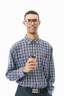 Retrato de um jovem feliz, vestindo uma camisa xadrez em pé sobre o branco, segurando uma xícara de café