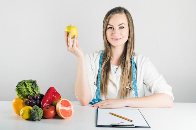 Retrato, de, um, jovem, femininas, dietician, segurando, maçã