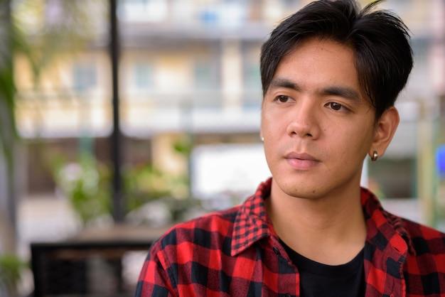 Retrato de um jovem filipino jovem e bonito relaxando dentro de uma cafeteria
