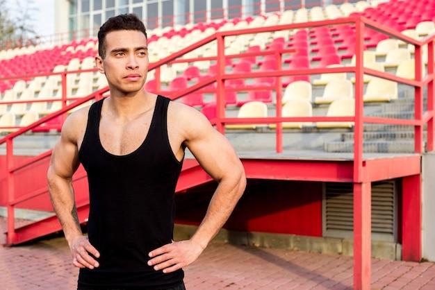 Retrato de um jovem fitness masculino em pé na frente da arquibancada