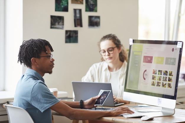 Retrato de um jovem fotógrafo afro-americano gerenciando o mercado de ações de fotos enquanto usa o computador na mesa do escritório com o site na tela, copie o espaço