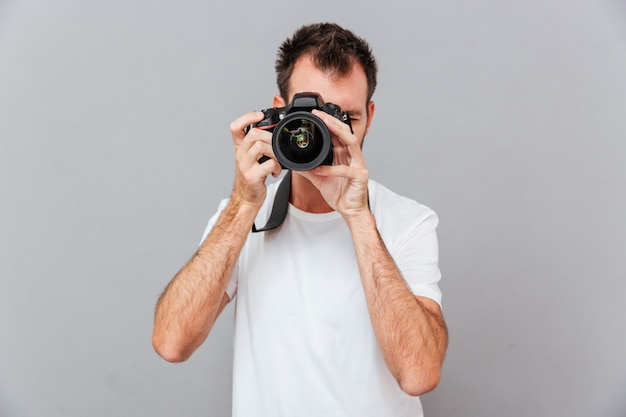 Retrato de um jovem fotógrafo com câmera isolada em um fundo cinza